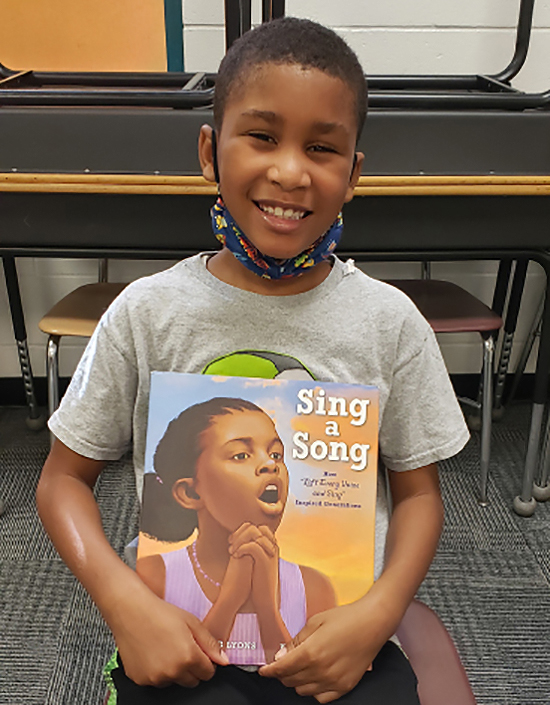 A child showing off Sing a Song, a book from the festival