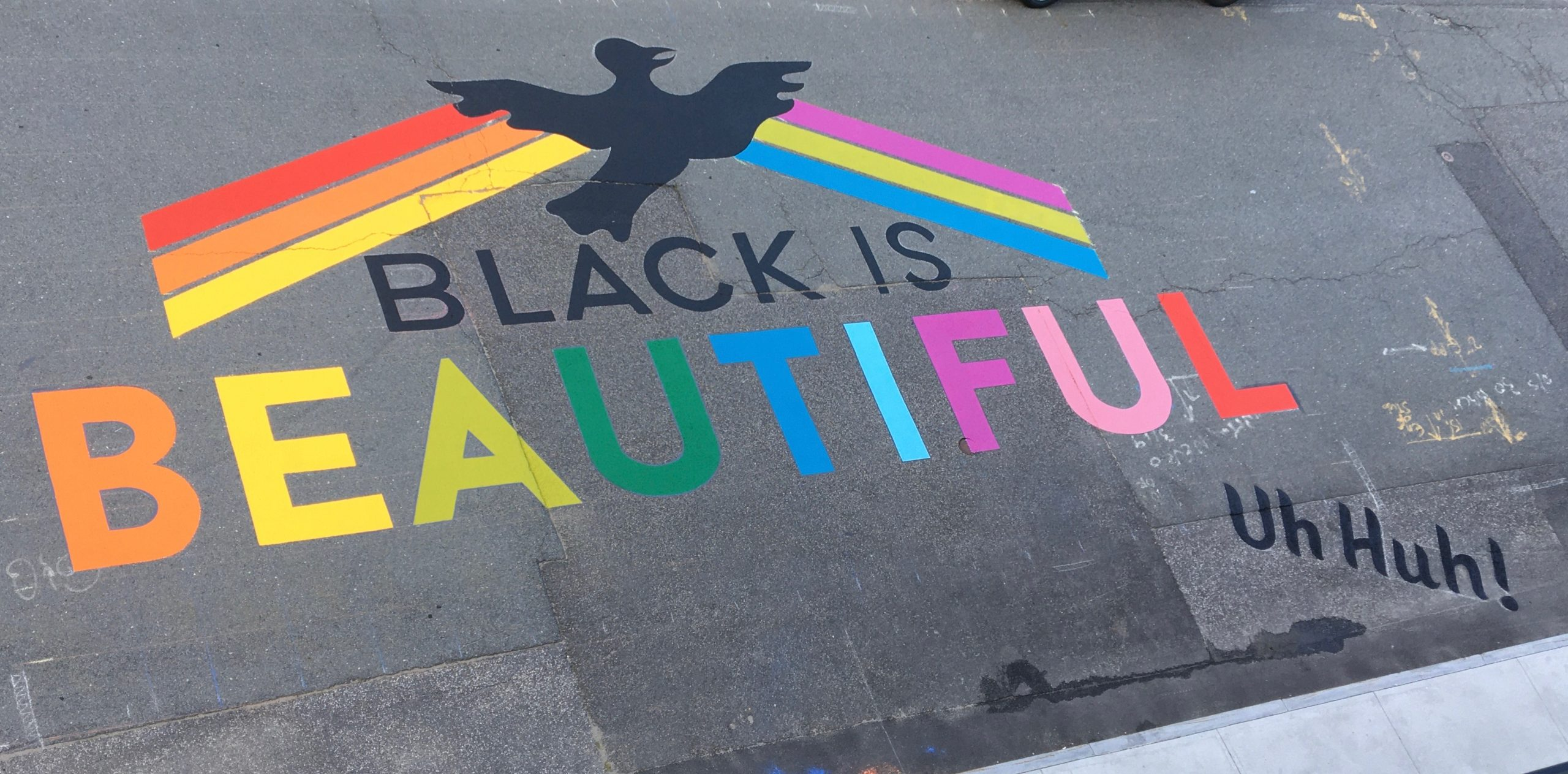 The Black is  Beautiful, Uh Huh! mural painted on the street